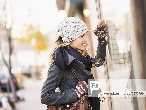 Portrait of blond woman looking at window display