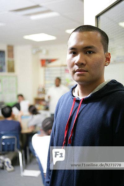 Teenage boy (15-17) standing in classroom  portrait