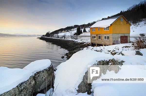 Felsbrocken Winter bedecken Küste Sonnenaufgang Fernverkehrsstraße frontal Norwegen Blockhaus typisch Atmosphäre Fjord Schnee Holzhaus