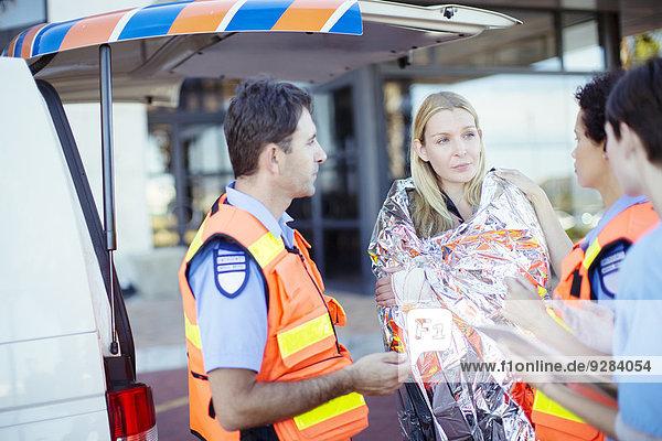 Sanitäter im Gespräch mit dem Patienten auf dem Krankenhausparkplatz