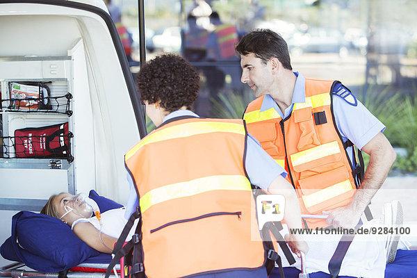 Rettungssanitäter bei der Untersuchung des Patienten auf der Trage