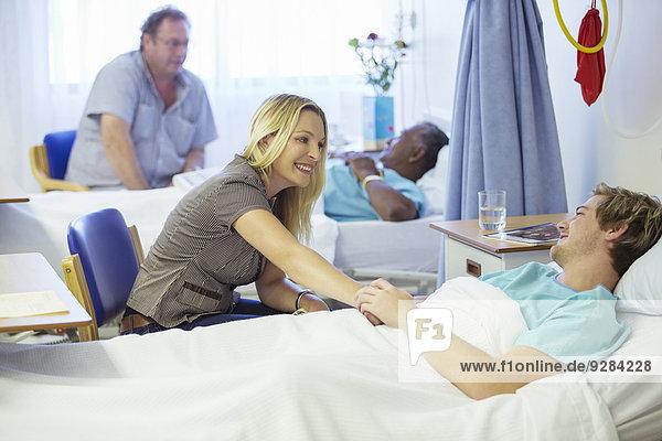Frau im Gespräch mit Freund im Krankenhaus