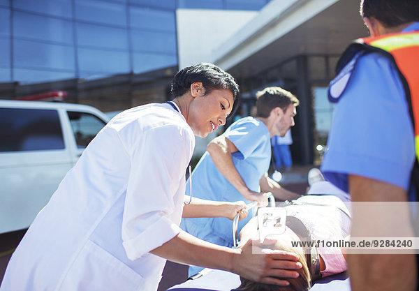 Arzt  Krankenschwester und Sanitäter  die den Patienten ins Krankenhaus bringen.