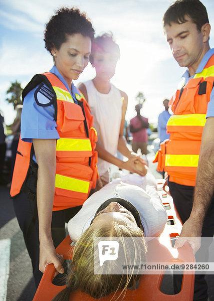 Rettungssanitäter  die den Patienten auf der Trage tragen