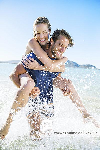 Frau reitet Huckepack auf Freund im Wasser
