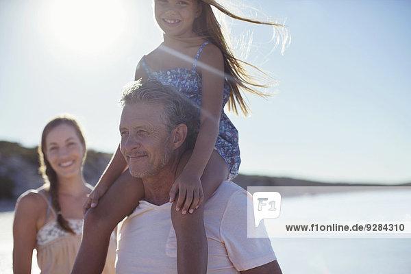 Vater hält Tochter auf Schultern am Strand