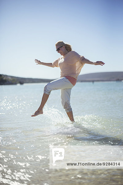Frau beim Planschen im Wasser am Strand