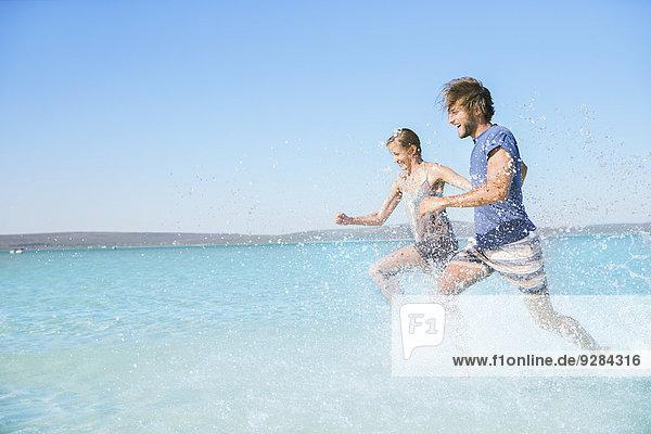 Paar  das am Strand im Wasser läuft