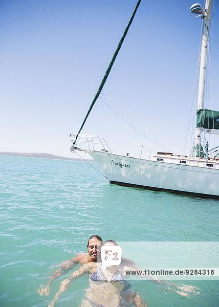 Paar beim Schwimmen im Wasser in der Nähe des Bootes