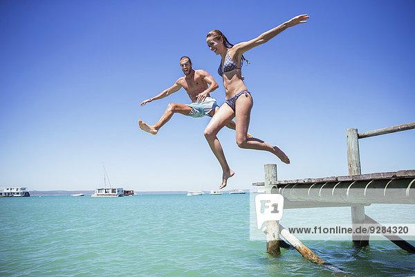 Paar springt vom Holzsteg ins Wasser