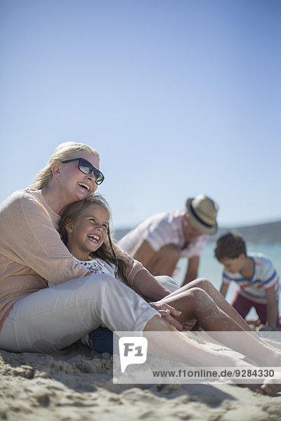 Gemeinsames Sitzen der Familie am Sandstrand