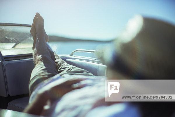 Mann entspannt sich auf dem Boot in Strandnähe
