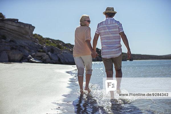 Ein Paar hält die Hände am Ufer entlang.