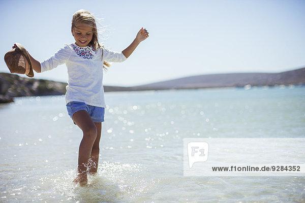 Junges Mädchen  das am Strand ins Wasser spritzt.