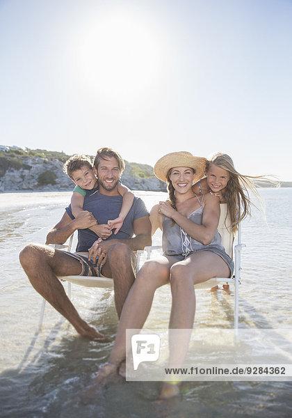 Familie auf Stühlen in Wellen sitzend