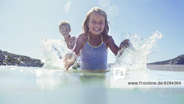 Junges Mädchen und Bruder beim Planschen im Wasser