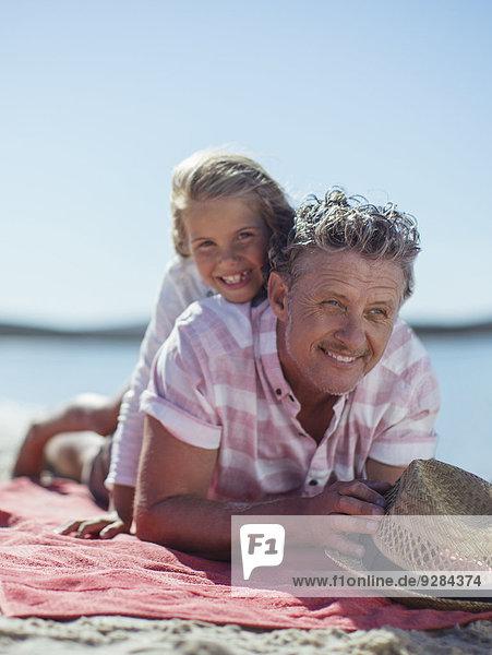 Großvater und Enkelin beim Spielen am Strand