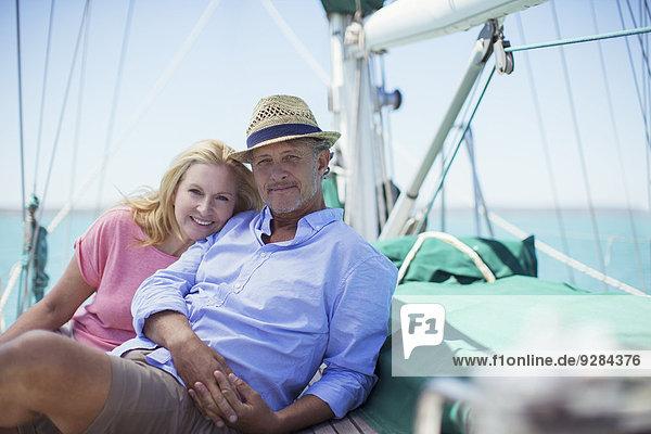 Paar auf Deck eines Segelbootes sitzend