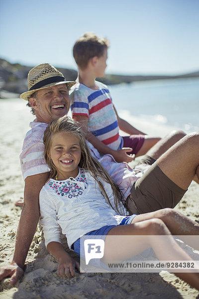Familie sitzt zusammen im Sand