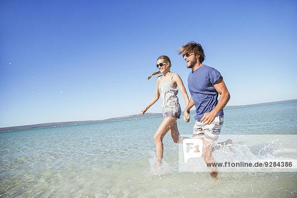 Paare  die zusammen im Wasser laufen