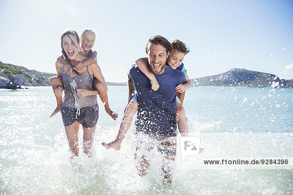 Familienlauf im Wasser am Strand