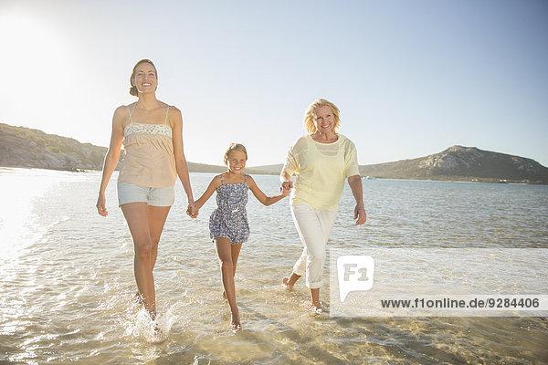 Drei Generationen von Frauen  die in Wellen gehen.
