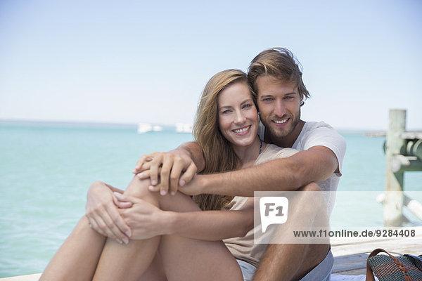 Paar sitzt zusammen auf der Kante eines Holzdocks