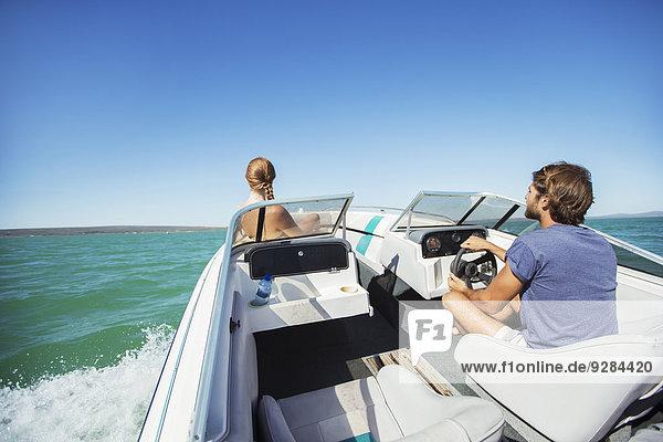 Mann steuert Boot auf dem Wasser mit Freundin
