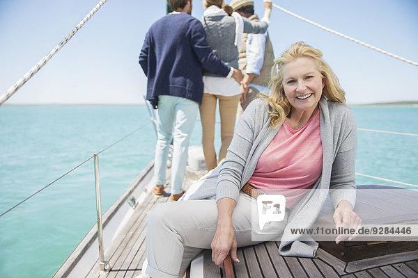 Ältere Frau sitzt auf dem Boot und entspannt sich mit der Familie.
