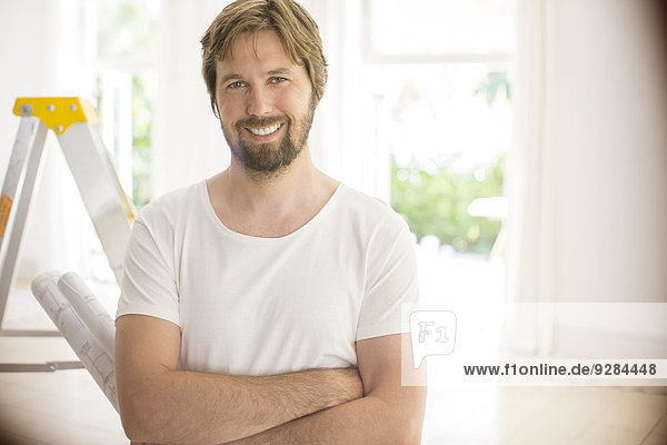 Man smiling near ladder in empty room