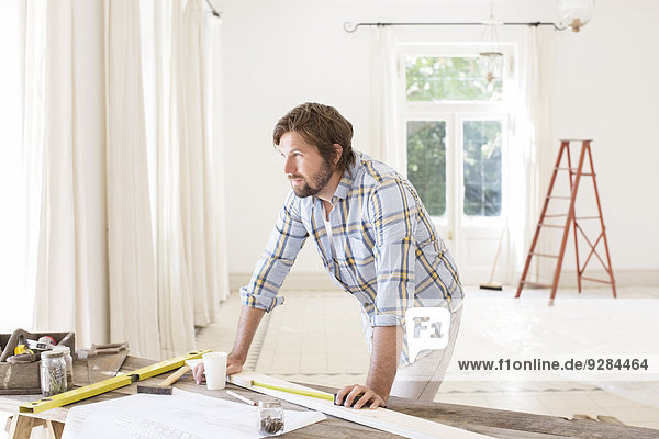 Man overlooking construction table in living space