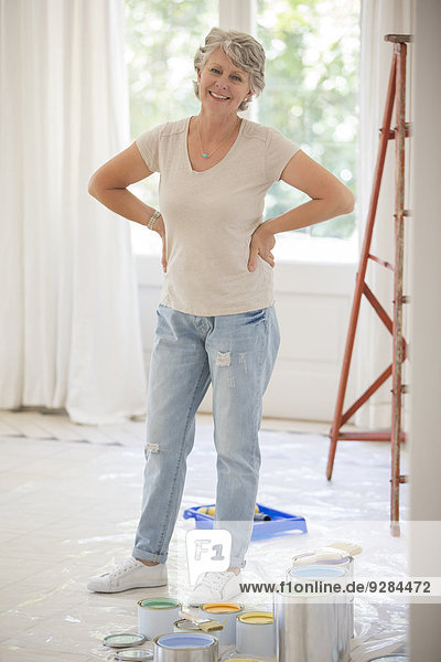 Older woman standing near paint in living space