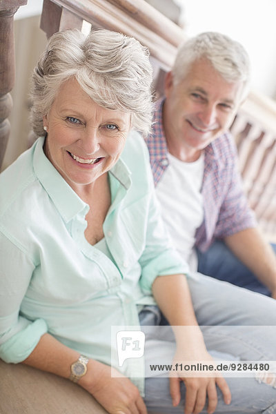 Older couple sitting together on stairs