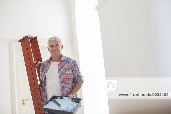 Older man carrying ladder and paint tray