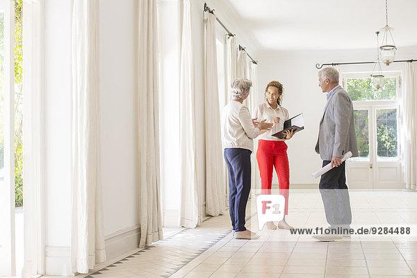 Älteres Paar im Gespräch mit Frau im Wohnraum