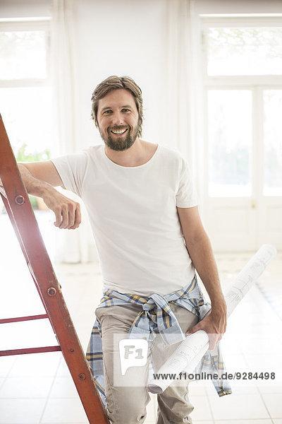 Mann steht auf Leiter im Wohnraum