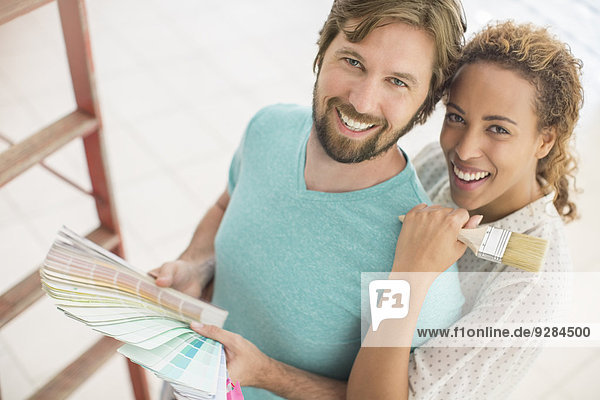 Couple looking through paint swatches together