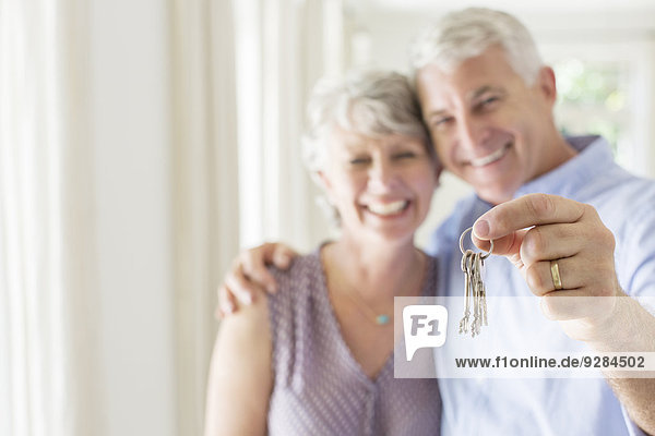 Older man holding keys with wife