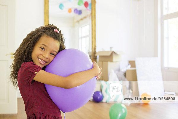 Young girl hugging purple balloon