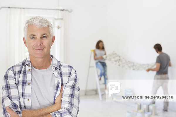 Older man smiling with family working