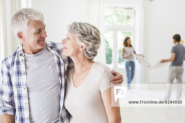 Older couple smiling together in living space
