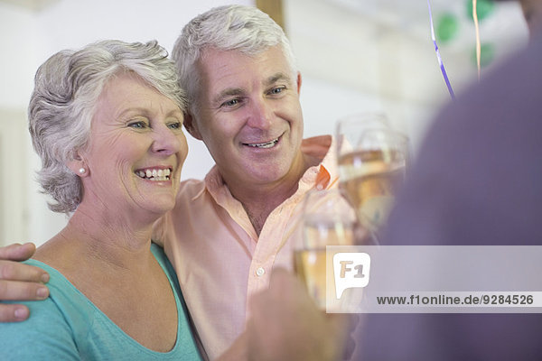 Older couple celebrating with drinks