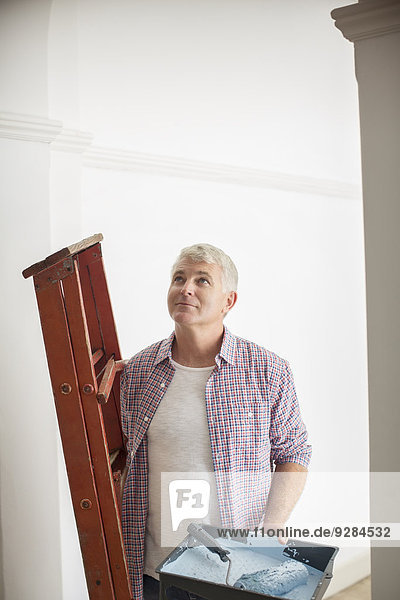 Man carrying ladder and paint tray