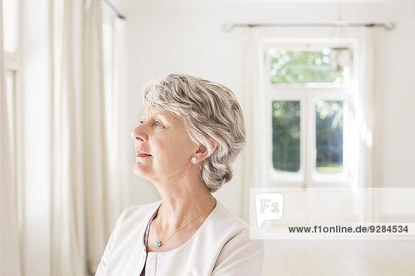 Ältere Frau mit Blick auf den Wohnraum