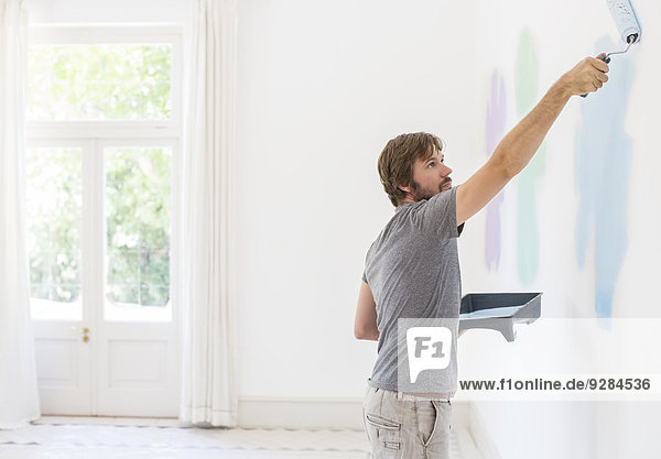 Man painting wall in living space