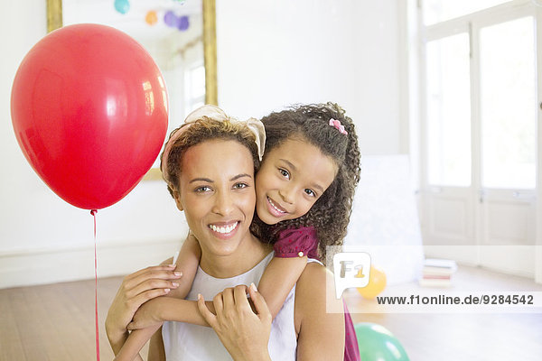 Mother and daughter hugging in living space