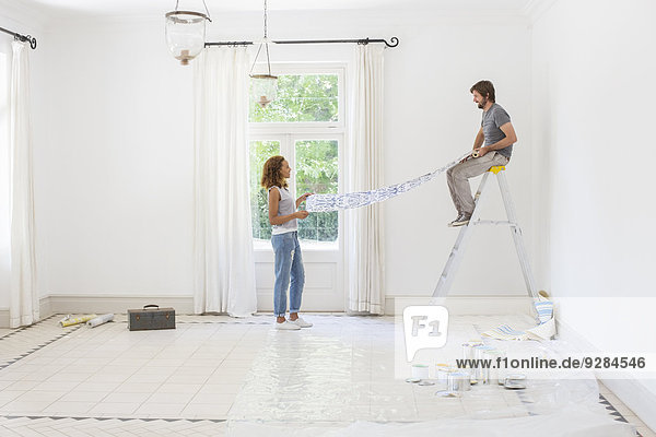 Couple laying out wallpaper together