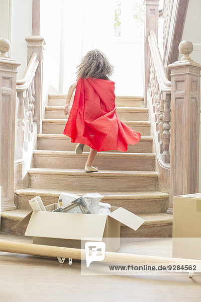 Young girl running up stairs playing
