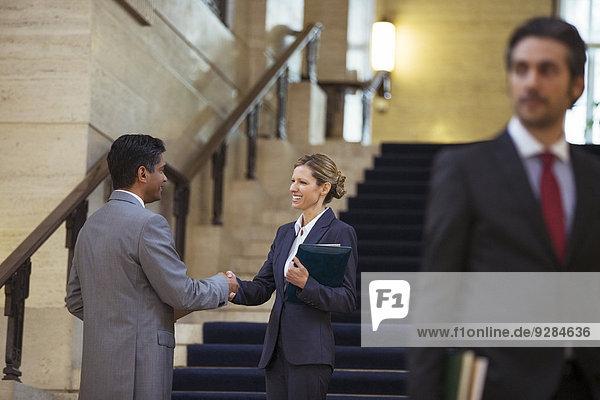 Anwälte beim Händeschütteln im Gerichtsgebäude