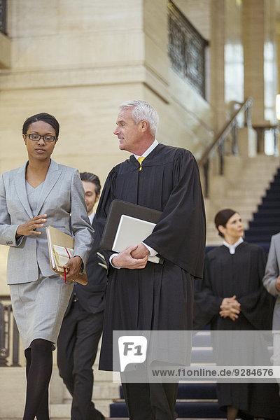 Richter und Anwalt gehen zusammen durch das Gerichtsgebäude.